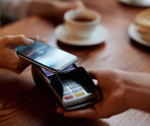 Handy wird an Terminal gehalten für mobiles Bezahlen