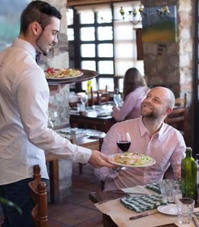 Kellner bringt essen zu Mann an Tisch