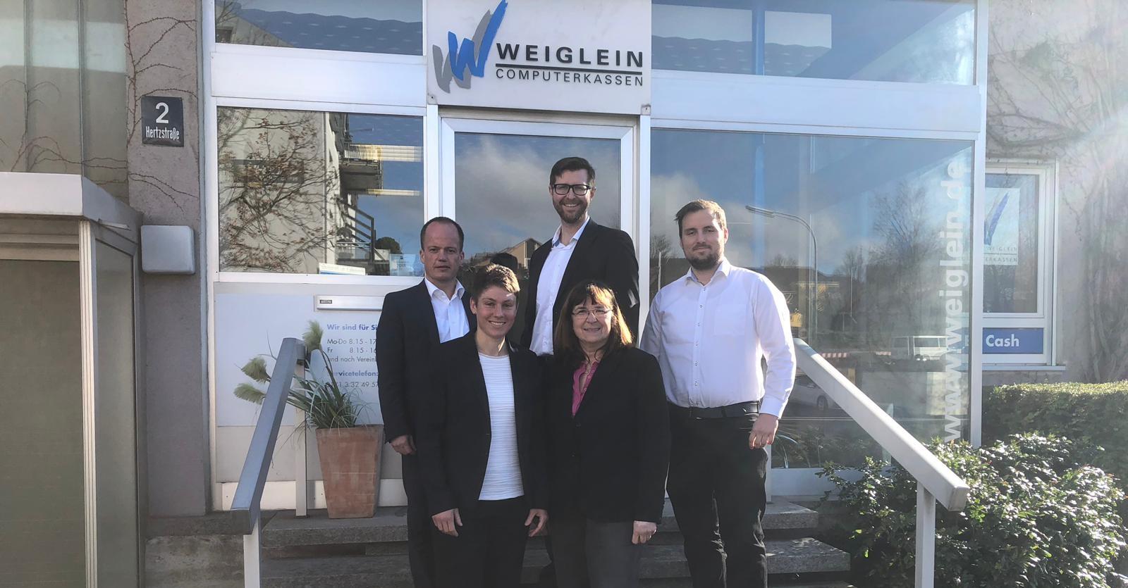 Verantwortliche der Volksbank in der Ortenau eG und Weiglein Computerkassen GmbH auf Treppe vor Geschäftsgebäude