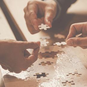 Drei Männer arbeiten gemeinsam an einem weißen Puzzle