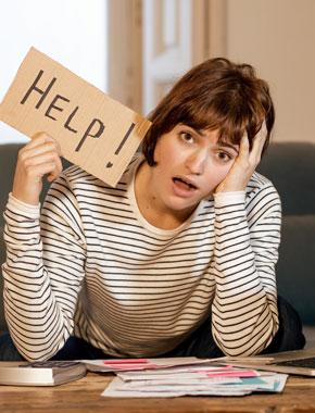 """Junge Frau verzweifelt vor Laptop mit """"Help""""-Schild"""