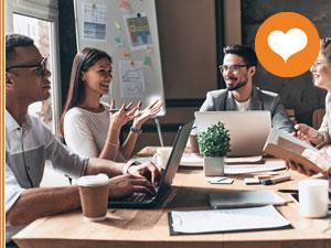 Drei Personen bei Teambesprechung mit Laptops, Block und Stift am Tisch